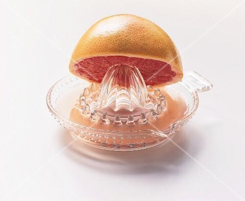 Pink grapefruit half on lemon squeezer with grapefruit juice