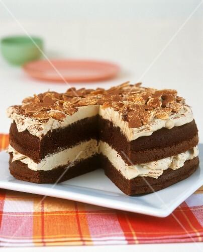 Chocolate cream gateau with flaked almonds, a piece cut