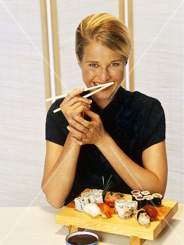 Cheerful blond woman eating sushi with chopsticks