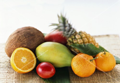 Exotic fruits, mandarins and coconut on a mat