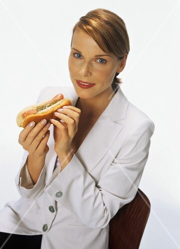 Young woman holding a hot dog