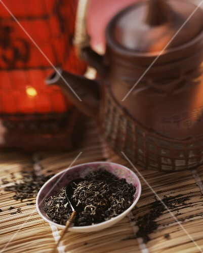 Black tea leaves in bowl, a teapot behind