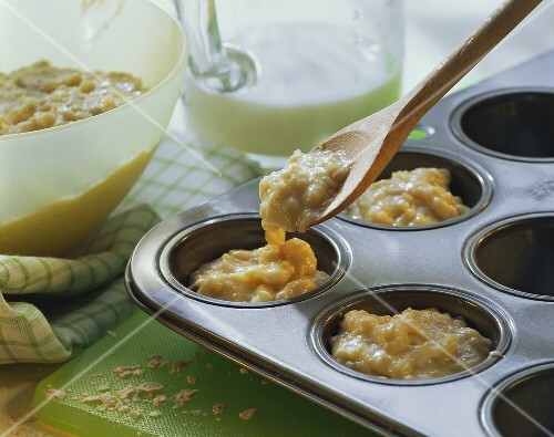 Making banana muffins (spooning the dough into muffin tins)