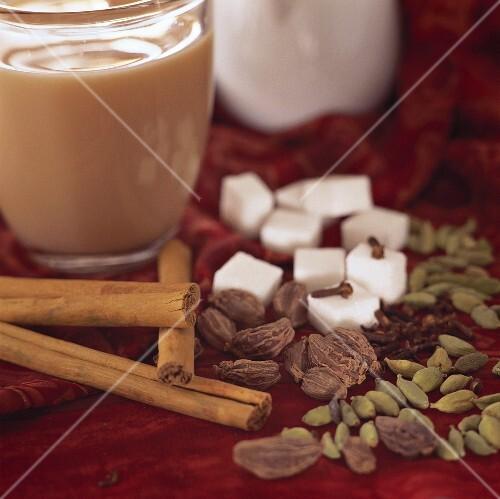 A glass of yogi tea, spices, sugar and milk jug beside it