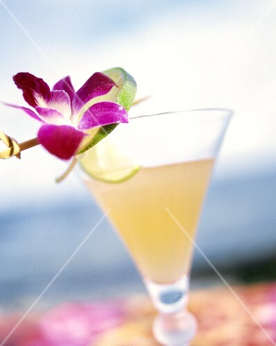 A glass of Daiquiri, garnished with lime peel & flower
