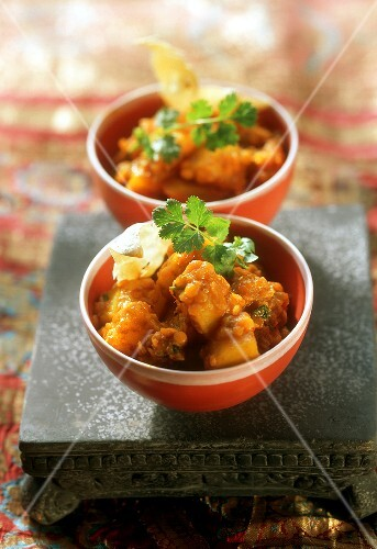 Two bowls of potato curry with red lentils