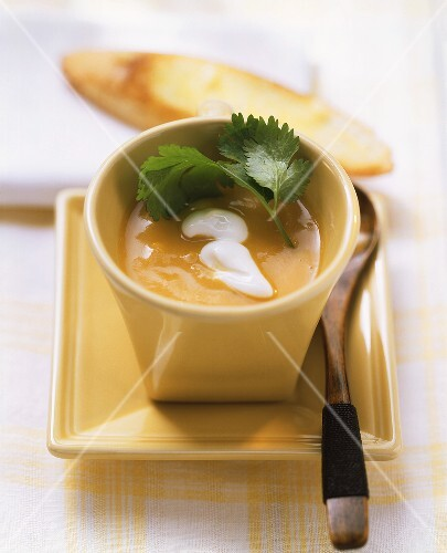 Pumpkin soup garnished with sour cream and coriander
