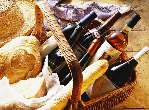 Basket with bottles of wine, hard cheese & white bread