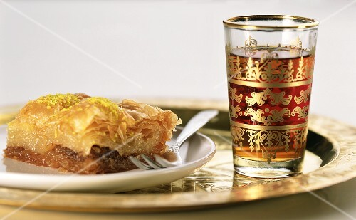 Stück Baklava auf einem Teller und Glas mit Tee