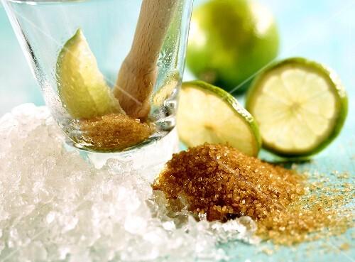 Cocktail-Symbolbild mit Glas, Zucker, Stössel und Limetten
