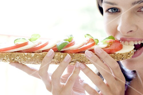 Young woman eating mozzarella and tomato sandwich