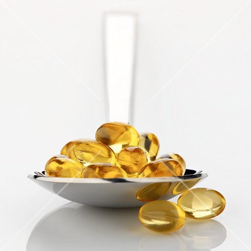 Vitamin E capsules on spoon