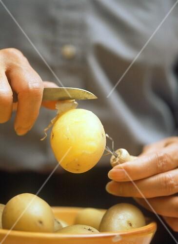 Kartoffeln mit Pellgabel und Messer pellen