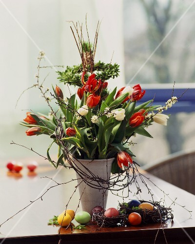 Spring bouquet of tulips in vase, Easter eggs beside it
