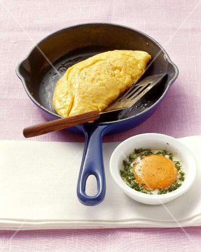 Omelett in einer Pfanne und gestocktes Ei im Förmchen