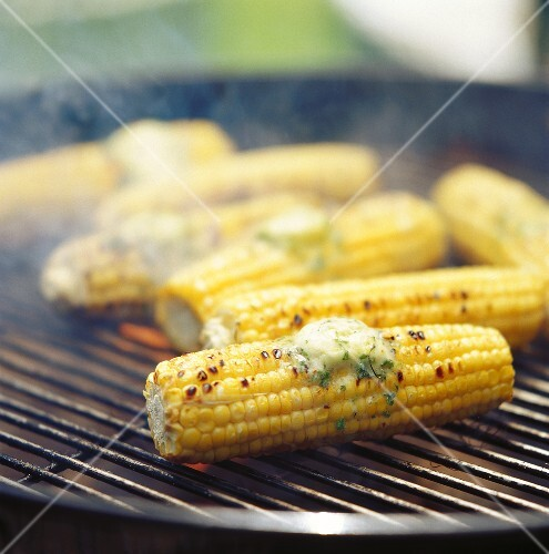 Corncobs with herb butter on the barbecue