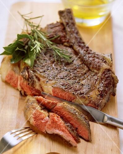 Peppered steak on a wooden board, cutlery beside it
