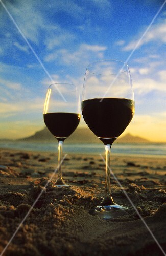 Red wine glasses on beach with mountain backdrop, S. Africa