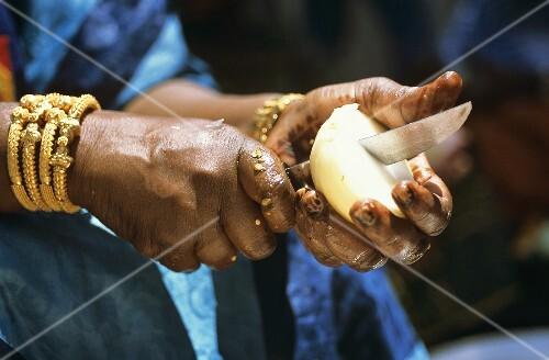 Schwarzafrikanische Frau zerschneidet eine Zwiebel