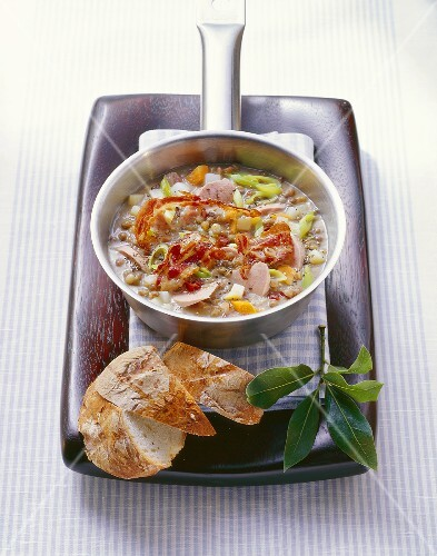 Lentil soup with bacon and sausage in small pan