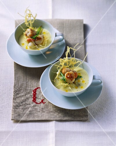 Two dishes of potato soup with scallops