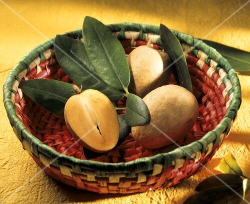 Whole and half sapodilla with leaves in a basket