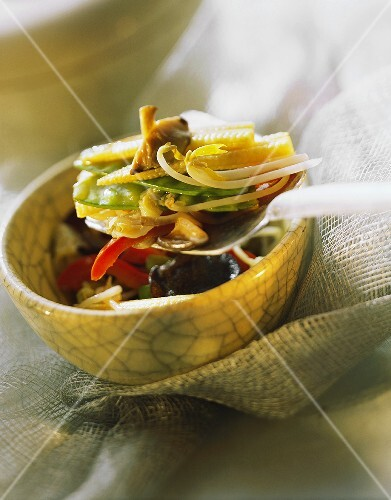 Stir-fried vegetables with spouts on spoon above bowl