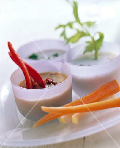 Vegetables (carrots, peppers) with three dips in bowls