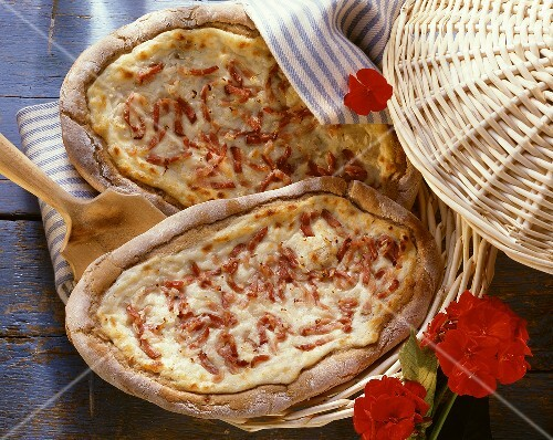 Two tartes flambées with bacon & onions in basket