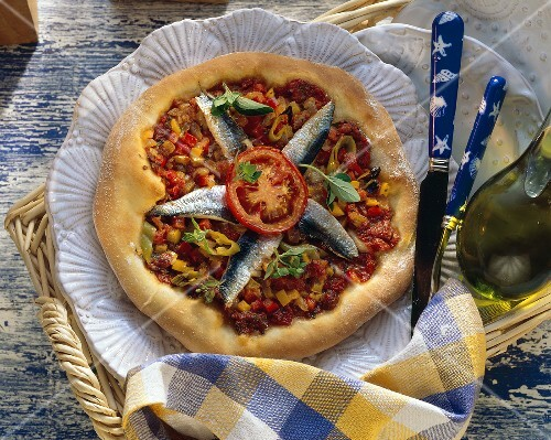 Whole sardine and tomato pizza on plate in wicker tray
