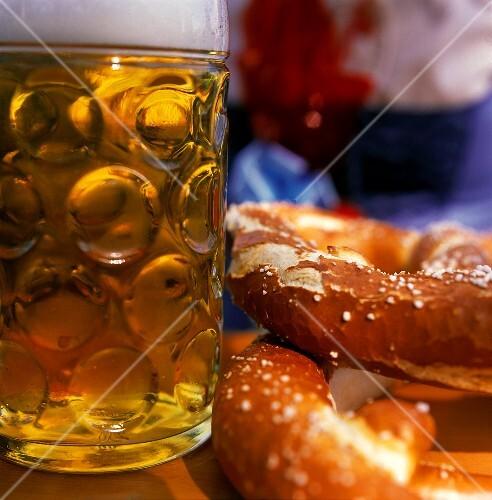 Tankard and two pretzels on table at Oktoberfest