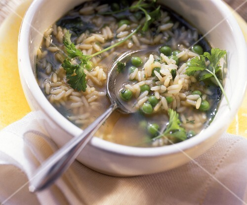 Rice soup with peas and fresh parsley