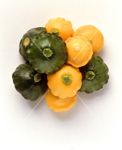 Yellow and green mini-patty pan squashes on white background