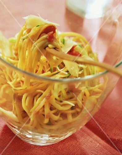 Linguine with vegetable strips in glass dish & on fork
