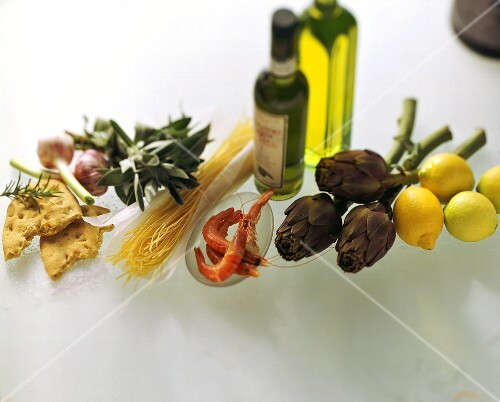 Still life with olive oil, vegetables, shrimps, lemons, noodles