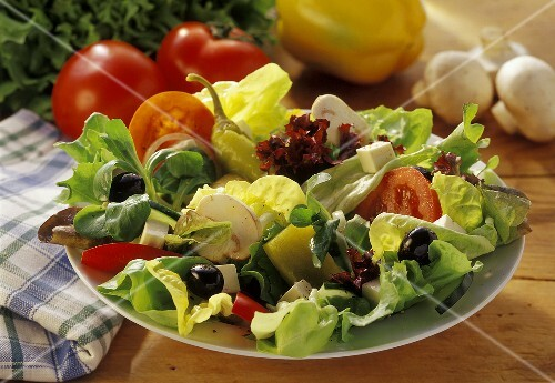 Mixed salad leaves on plate, vegetables behind