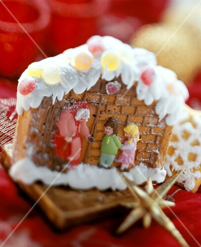 Gingerbread house with fairytale figures on red cloth