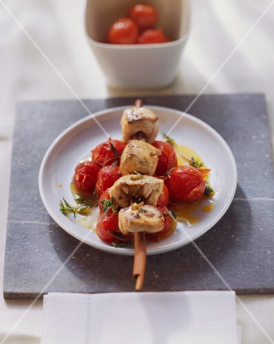 Poulard on cinnamon skewer on saffron tomatoes with thyme
