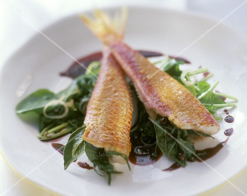 Red mullet on spinach in red wine with onions