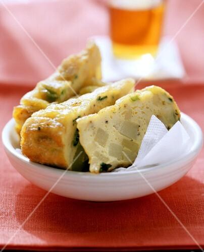 Pieces of potato tortilla with napkin in white bowl