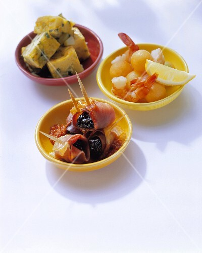 Three different tapas in colourful bowls