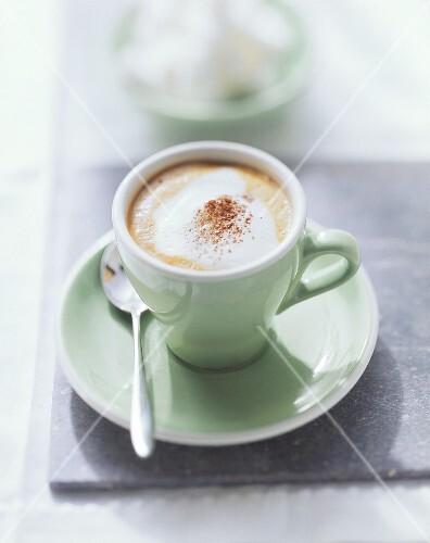 Cappuccino with cocoa powder in pale green espresso cup