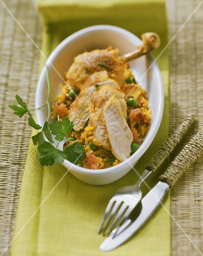 Chicken with saffron rice and parsley in a baking dish