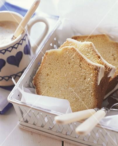 Iced Madeira cake beside coffee cup