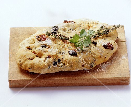 Focaccia with olives and dried tomatoes on wooden board