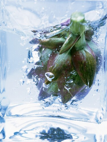 Artichoke in glass container of boiling water