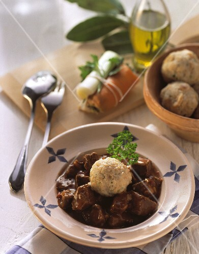 A plate of goulash with bread dumplings