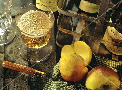 A glass of cider; apples and cider bottles