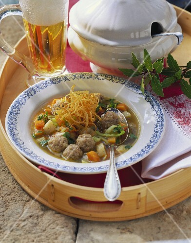 Root vegetable stew with pork dumplings; glass of beer