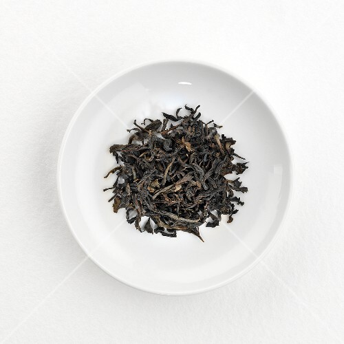 Green tea leaves (Golden Oolong, China) on plate